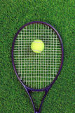 Tennis raquet and ball on grass. A tennis raquet or racket and yellow ball on grass royalty free stock photo