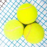 Tennis raquet with a tennis balls. Close up of three tennis balls on a tennis raquet royalty free stock photo