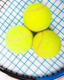 Tennis raquet with a tennis balls. Close up of three tennis balls on a tennis raquet royalty free stock photography