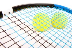 Tennis raquet with a tennis balls. Close up of two tennis balls under a tennis raquet Stock Photography