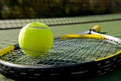 Tennis-Schläger und Kugel auf Gericht Stockfotos