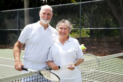 Tennis Senior Couple. Portrait of a happy senior couple on the tennis courts Royalty Free Stock Photo