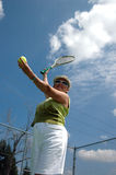 Tennis serve. An active senior woman on the tennis court preparing to serve royalty free stock photography
