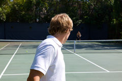 Tennis Serve across the court. With a white shirt waist up Royalty Free Stock Photo