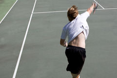 Tennis Serve Motion Blur. With white shirt and black shorts Royalty Free Stock Images