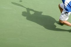 Tennis shadow 01. The shadow of a man playing tennis on a court Stock Images