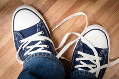 Tennis shoes. Classic tennis shoes on the wooden floor royalty free stock images