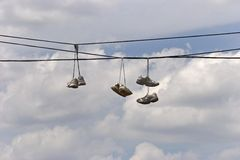 Tennis shoes in gang territory. Three pair of tennis shoes over powerlines signifying gang territory Stock Photography