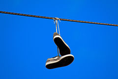 Tennis shoes hanging from a power line. Against clear blue sky stock photos