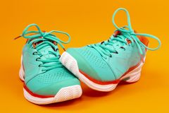 Tennis shoes in studio. Red, cyan, white pair of new tennis shoes in studio isolated on an orange background royalty free stock images
