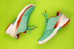 Tennis shoes in studio. Red, cyan, white pair of new tennis shoes in studio shot over green background. Directly from above stock image