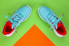 Tennis shoes in studio. Red, cyan, white pair of new tennis shoes in studio shot over green and orange background. Directly from above stock image