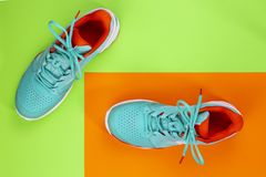 Tennis shoes in studio. Red, cyan, white pair of new tennis shoes in studio shot over green, orange background. Directly from above royalty free stock photo