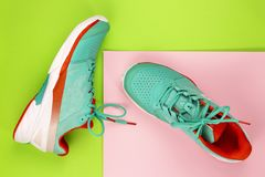 Tennis shoes in studio. Red, cyan, white pair of new tennis shoes in studio shot over green, pink background. Directly from above stock photo