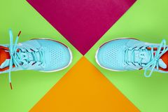 Tennis shoes in studio. Red, cyan, white pair of new tennis shoes in studio shot over green, pink, purple background. Directly from above royalty free stock images
