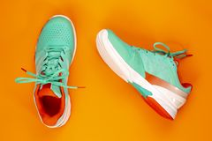 Tennis shoes in studio. Red, cyan, white pair of new tennis shoes in studio shot over orange background. Directly from above royalty free stock image