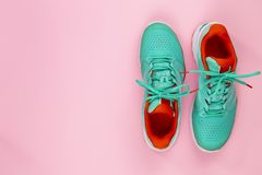 Tennis shoes in studio. Red, cyan, white pair of new tennis shoes in studio shot over pink background. Directly from above royalty free stock images