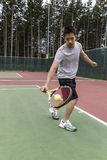 Tennis Single handed backhand. Young Asian Man using single handed backhand on outdoor tennis court Stock Photography