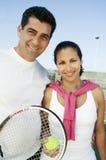 Tennis-Spieler der gemischten Doppeln, die auf Tennisplatzporträt stehen lizenzfreie stockfotografie