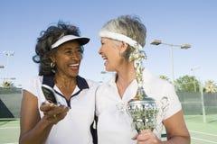Tennis-Spieler mit der Trophäe, die Handy hält Stockfoto