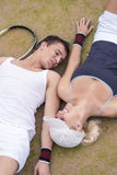 Tennis Sport Concept: Young Couple of tennis Players Resting On. Tennis Court and Smiling. Vertical Image Stock Photo