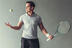 Tennis. Sport, lifestyle and people concept - young man tennis player in action on gray background stock images