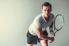 Tennis. Sport, lifestyle and  people concept - young man tennis player in action on gray background Stock Photos
