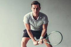 Tennis. Sport, lifestyle and  people concept - young man tennis player in action on gray background Stock Photo