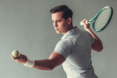 Tennis. Sport, lifestyle and people concept - young man tennis player in action on gray background royalty free stock images