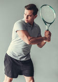 Tennis. Sport, lifestyle and  people concept - young man tennis player in action on gray background Royalty Free Stock Photos