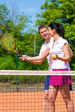 Tennis sport teacher teaching woman to play Stock Photography