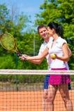 Tennis sport teacher teaching woman to play. Man, tennis sport teacher, teaching women how to play the racket sport outdoors Stock Photography