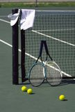 Tennis Still Life. Rackets balls towel and hat on tennis court by the net Stock Photos