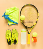 Tennis stuff on cream background. Sport, fitness, tennis, healthy lifestyle, sport stuff. Tennis racket, lime trainers, tennis bal Stock Images