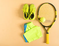 Tennis stuff on cream background. Sport, fitness, tennis, healthy lifestyle, sport stuff. Tennis racket, lime trainers, tennis bal. Ls, lime athletic shorts royalty free stock photos
