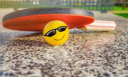 Tennis table paddle with a smiley ball royalty free stock image