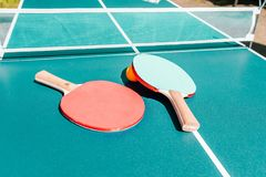 Tennis table with rackets. Bright green table with orange ball and white net. Activities and sports. Banner in a sports shop. The stock photography