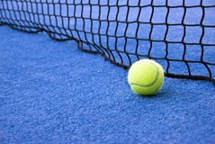 Tennis time. Details of tennis ball and net, natural light, blue grass Royalty Free Stock Images