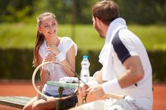 Tennis trainer with girl player on break. Tennis trainer with girl player enjoy and chatting on break Royalty Free Stock Photo