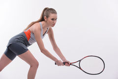 Tennis woman player with racket. I am in game. Beautiful young woman in sports clothes holding tennis racket and looking  away while standing against white Stock Photography