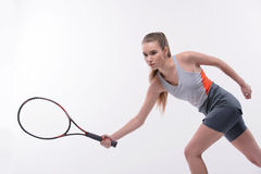 Tennis woman player with racket. I am in game. Beautiful young woman in sports clothes holding tennis racket and looking  away while standing against white Royalty Free Stock Photo