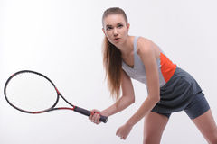 Tennis woman player with racket. I am in game. Beautiful young woman in sports clothes holding tennis racket and looking up while standing against white Stock Image