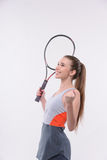 Tennis woman player with racket. I am the winner. Rear view of beautiful happy young woman in sports clothes holding tennis racket and raising hands  while Royalty Free Stock Photos