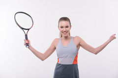 Tennis woman player with racket. I am the winner. Rear view of beautiful happy young woman in sports clothes holding tennis racket and raising hands  while Royalty Free Stock Image