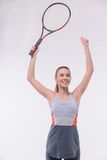 Tennis woman player with racket. I am the winner. Rear view of beautiful happy young woman in sports clothes holding tennis racket and raising hands  while Royalty Free Stock Photography