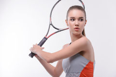 Tennis woman player with racket. Ready to serve. Beautiful young woman in sports clothes holding tennis racket and looking away while standing against white Royalty Free Stock Image