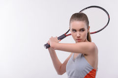 Tennis woman player with racket. Ready to serve. Beautiful young woman in sports clothes holding tennis racket and looking away while standing against white Royalty Free Stock Images