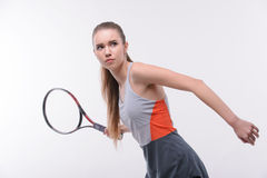 Tennis woman player with racket. Ready to serve. Beautiful young woman in sports clothes holding tennis racket and looking away while standing against white Stock Images