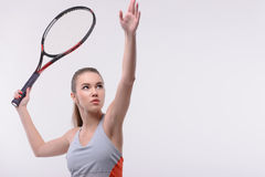 Tennis woman player with racket. Ready to serve. Beautiful young woman in sports clothes holding tennis racket and looking up while standing against white Stock Photos