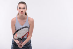 Tennis woman player with racket. Ready to win. Beautiful young woman in sports clothes holding tennis racket and looking at camera while standing against white Royalty Free Stock Images